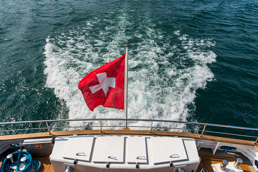 Wake and Swiss flag swaying in the wind on ship, Geneva, Switzerland