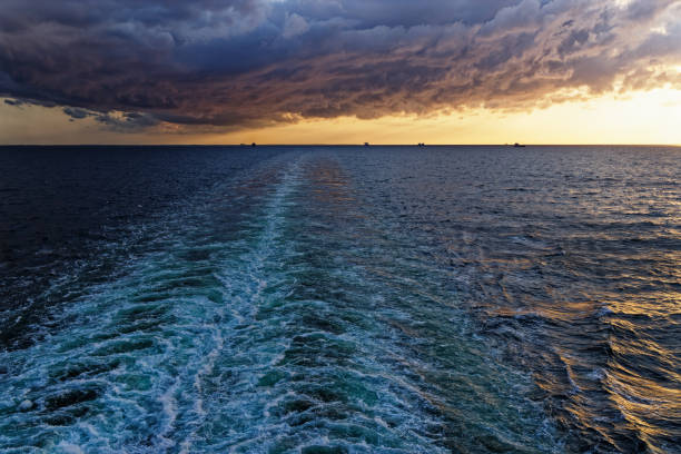 Wake of a cruise ship during sunset stock photo