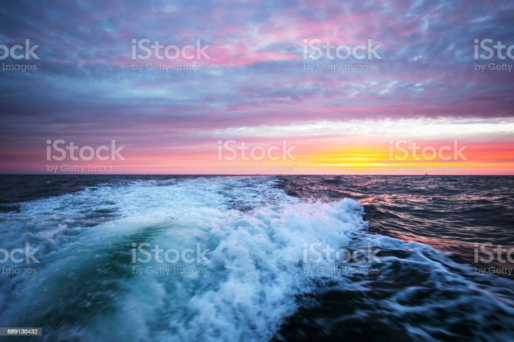 A wake of a motorboat at sunset time stock photo