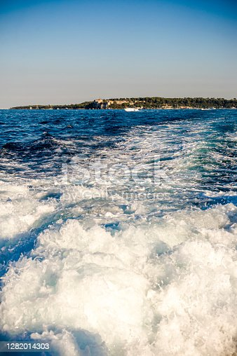 View of the Wake of a ship leaving the Iles St Marguerite, part of Iles de Lerins, and going back to the city of Cannes, France.