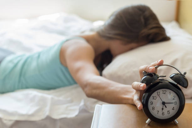 wake up of a girl stopping alarm clock - alarm stock pictures, royalty-free photos & images