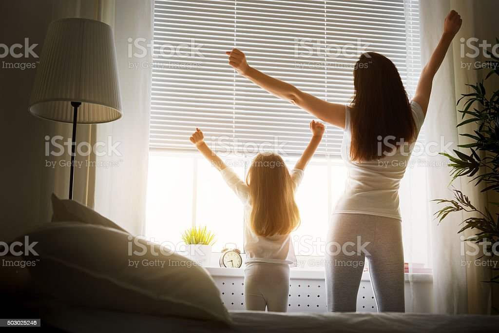 wake up mother and daughter enjoying sunny morning Adult Stock Photo