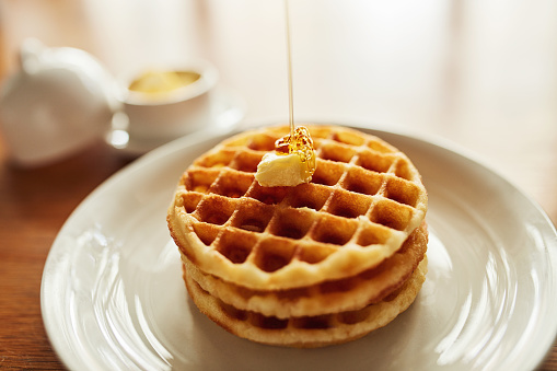 Shot of a stack of waffles topped with a cube of butter and syrup on a plate