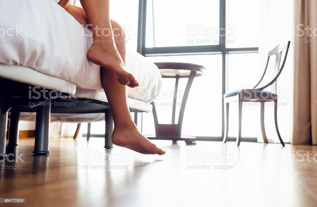 Wake up woman - close up image woman legs in bedroom stock photo