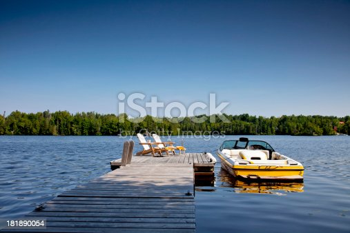 Two Adirondack chairs on Sunny Dock with Wakeboard boat. Horizontal.