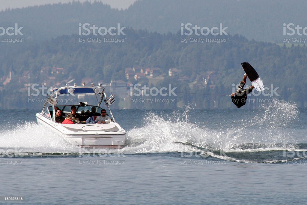 A wakeboarder in the water being pulled by a boat stock photo