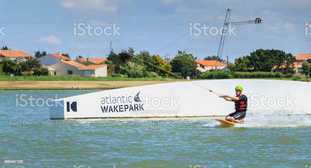 wakeboarder is exerted on the lake to make figures stock photo