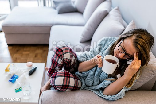 Upper view of Sick woman with a headache sitting on a sofa at home wrapped in blanket during the day. Sickness, seasonal virus problem concept. Woman being sick having flu lying on sofa, drinking tea with eyes closed.