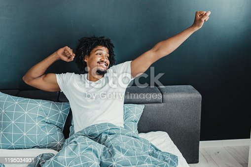 Young man in the morning waking up and stretching
