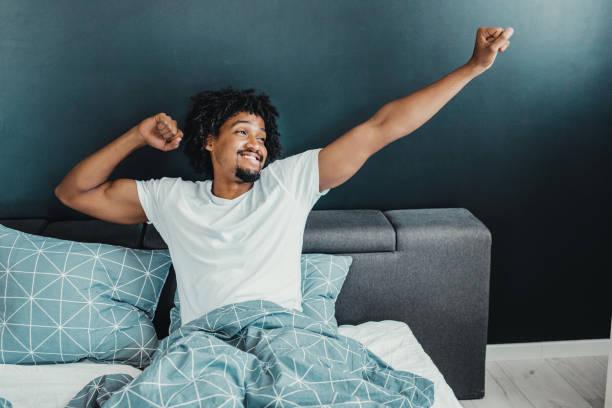 despertar con una sonrisa - man sleeping fotografías e imágenes de stock