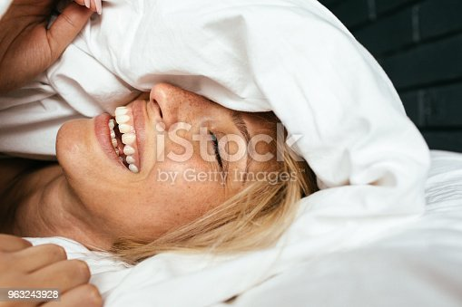 Portrait of a young beautiful woman waking up among the bed sheets, with a smile on her face