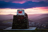 Welsh dragon monument with rolling hills and rural town backdrop - Brecon, Wales