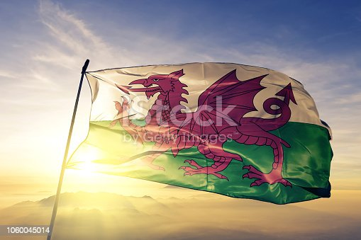 Wales Welsh United Kingdom Great Britain flag on flagpole textile cloth fabric waving on the top sunrise mist fog