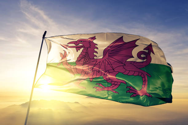 Wales Welsh United Kingdom Great Britain flag textile cloth fabric waving on the top sunrise mist fog Wales Welsh United Kingdom Great Britain flag on flagpole textile cloth fabric waving on the top sunrise mist fog wales stock pictures, royalty-free photos & images