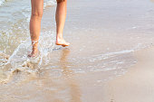 Couple legs in sand close up on sunny beach. Couple in love relaxing together on sandy seashore. Family summer vacation or honeymoon precious moments. Authentic image