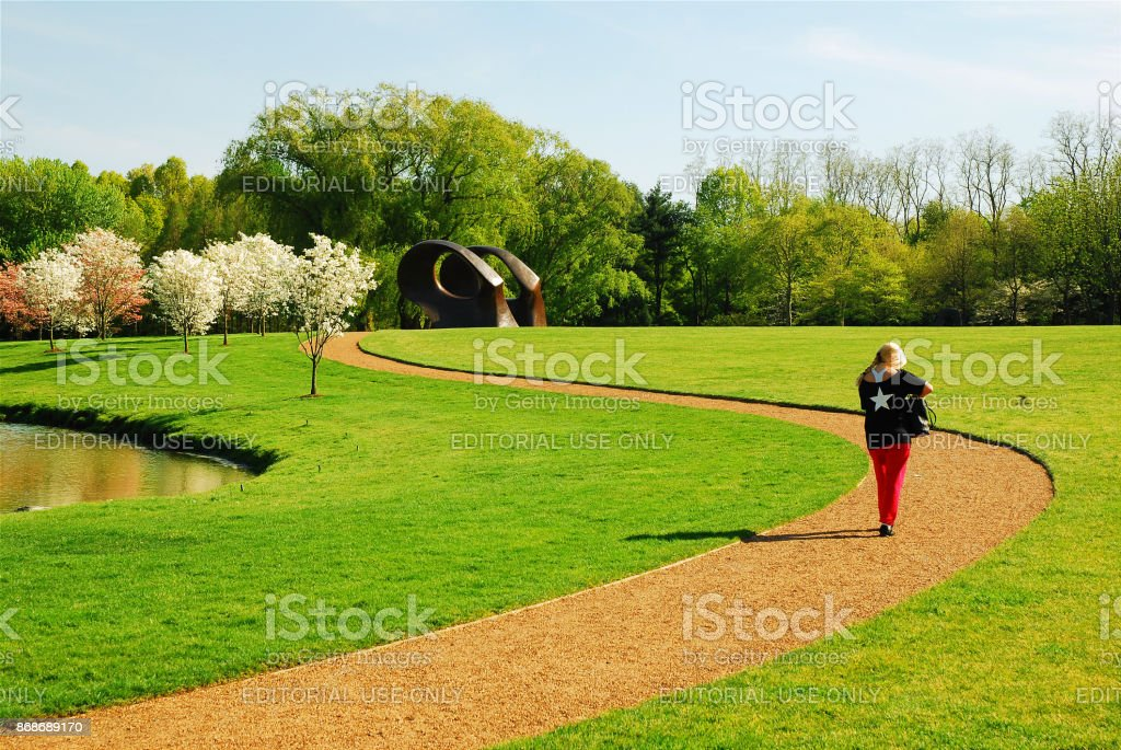 A walk among the spring trees and works of art stock photo