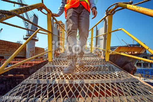 legs of worker or engineering wearing Safety shoes walking in mind step on the steel gangway bridge cross over at workplace, working in high stage and high level of insurance