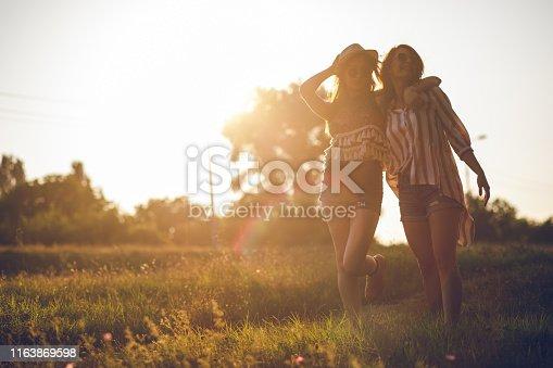 Two young caucasian women walking in a public park and having fun.