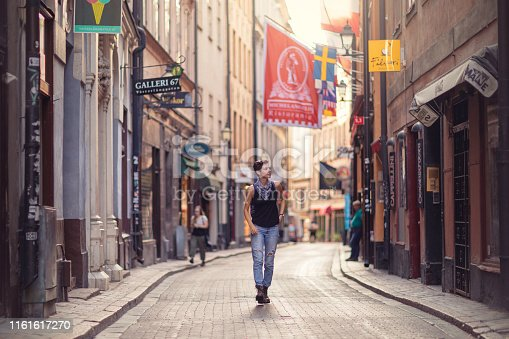 A woman walks down one of the main streets (Västerlånggatan) in the old town of Stockholm, Sweden, on a summer morning.