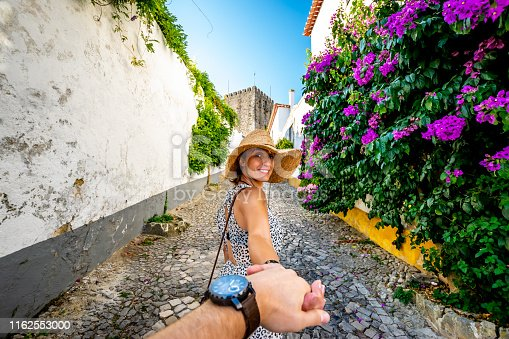 A woman reaches back to her husband's hand and entices him to walk through the old town of Obidos discovering the narrow colorful streets and it's old structures.