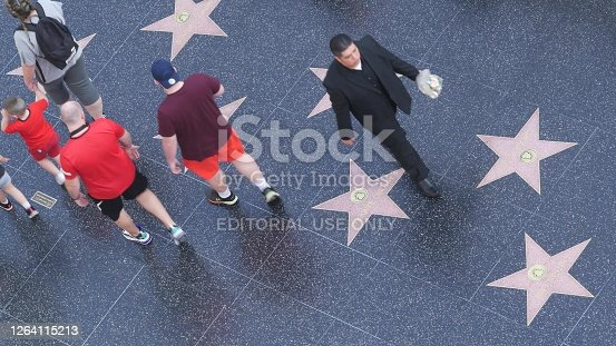 LOS ANGELES, CALIFORNIA, USA - 7 NOV 2019: Walk of fame promenade on Hollywood boulevard in LA. Pedastrians walking near celebrity stars on asphalt. Walkway floor near Dolby and TCL Chinese Theatre.