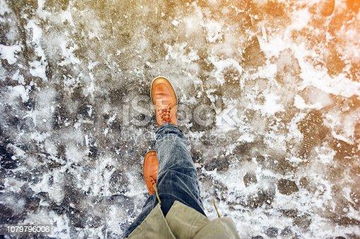 istock Walk on icy winter pavement background 1079796006