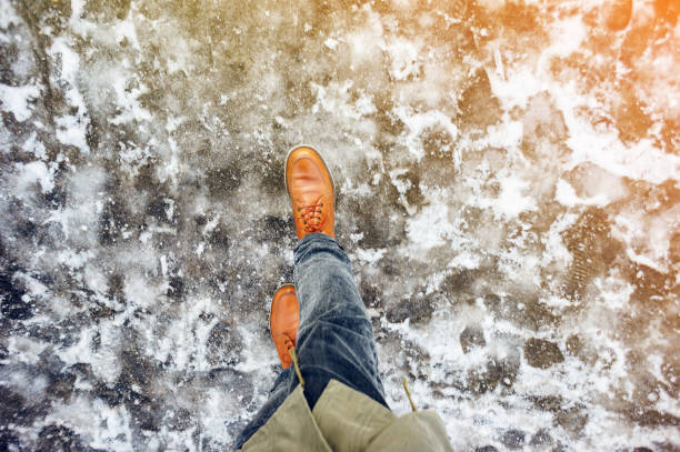 Walk on icy winter pavement background Walk on wet melted ice pavement. First person view on the feet of a man walking along the icy pavement. Pair of shoe on icy road in winter. Abstract empty blank winter weather background slippery stock pictures, royalty-free photos & images