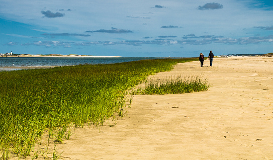 Barnstable, Massachusetts, USA - September 23, 2015: A young couple take a walk along an empty Cape Cod beach in Barnstable, Massachusetts on a September afternoon enjoying early Autumn weather and the view on Sand Neck Lighthouse on the left.