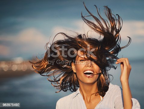 Closeup front view of an attractive mid 20's brunette walking on the beach at sunset and flirting with the camera. Her hair is flying and sparkling in the sun.