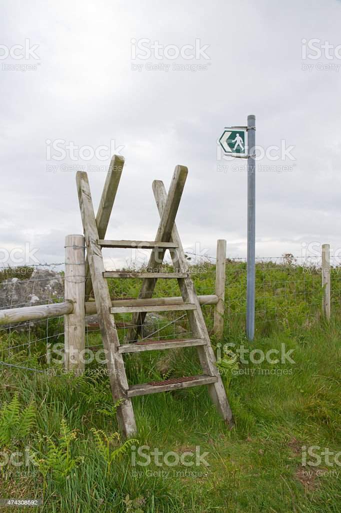 Walk this way, waymarker and stile on public footpath.. stock photo
