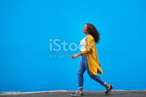 Full length shot of an attractive young woman walking against a blue background