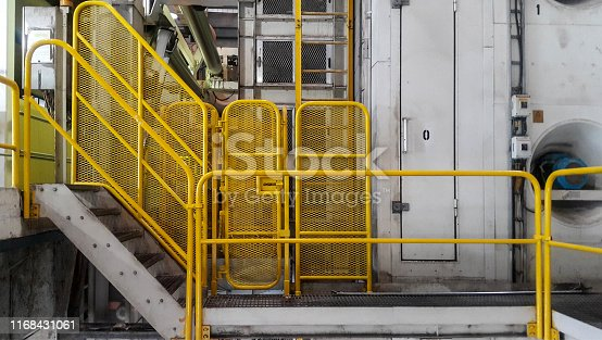 Walk way with yellow handrail inside factory