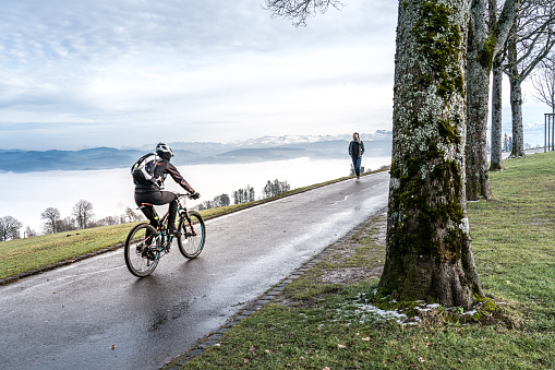 Walkers and cyclists on the Gurten Kulm, the local mountain of the city of Bern. In the background sea of fog and the Bernese Alps covered with snow, Switzerland.