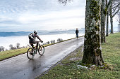 Bern, Switzerland - January 3, 2020: A Walker and a cyclist on the Gurten Kulm, the local mountain of the city of Bern. In the background a sea of fog and the Bernese Alps covered with snow, Switzerland.