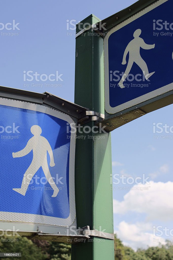 Walkers in the sky Road sign: pedestrian routes, against blue sky Anthropomorphic Stock Photo