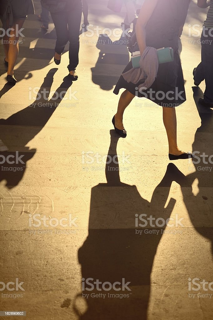 Walkers with the sunset in the background casting shadows royalty-free stock photo