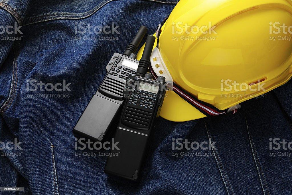 Walkie-Talkies and construction hard hat on denim jacket stock photo