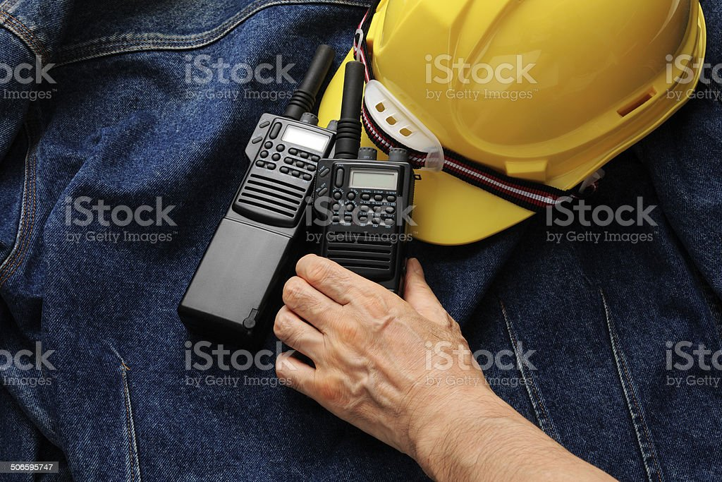 Walkie-Talkies and construction hard hat with hand on denim jacket stock photo