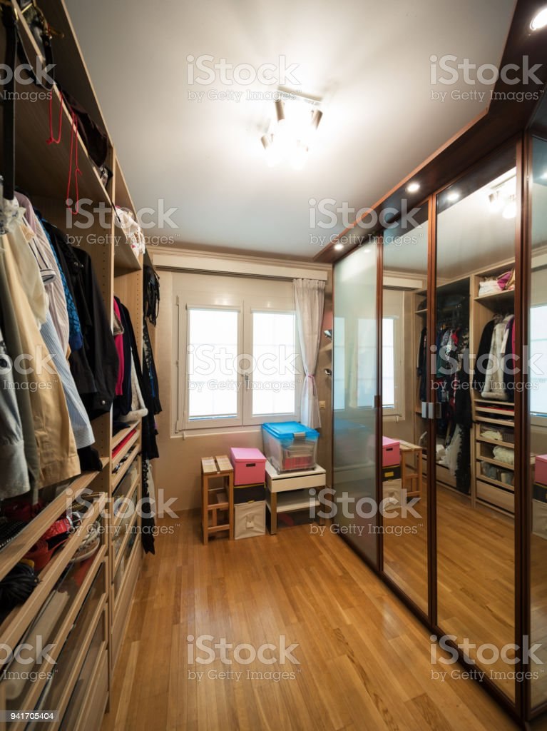 walk-in closet with clothes, parquet floor stock photo