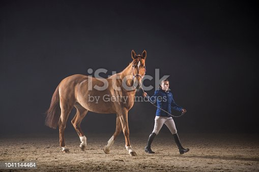 Young female jockey walking her racing horse.