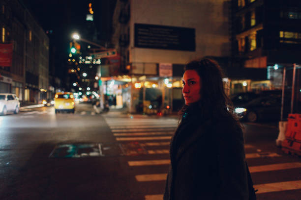 walking alone in New York City at night stock photo