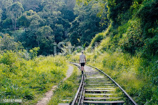 A young man walks along a train track surrounded by lush foliage whilst in Ella, Badulla District, Sri Lanka.