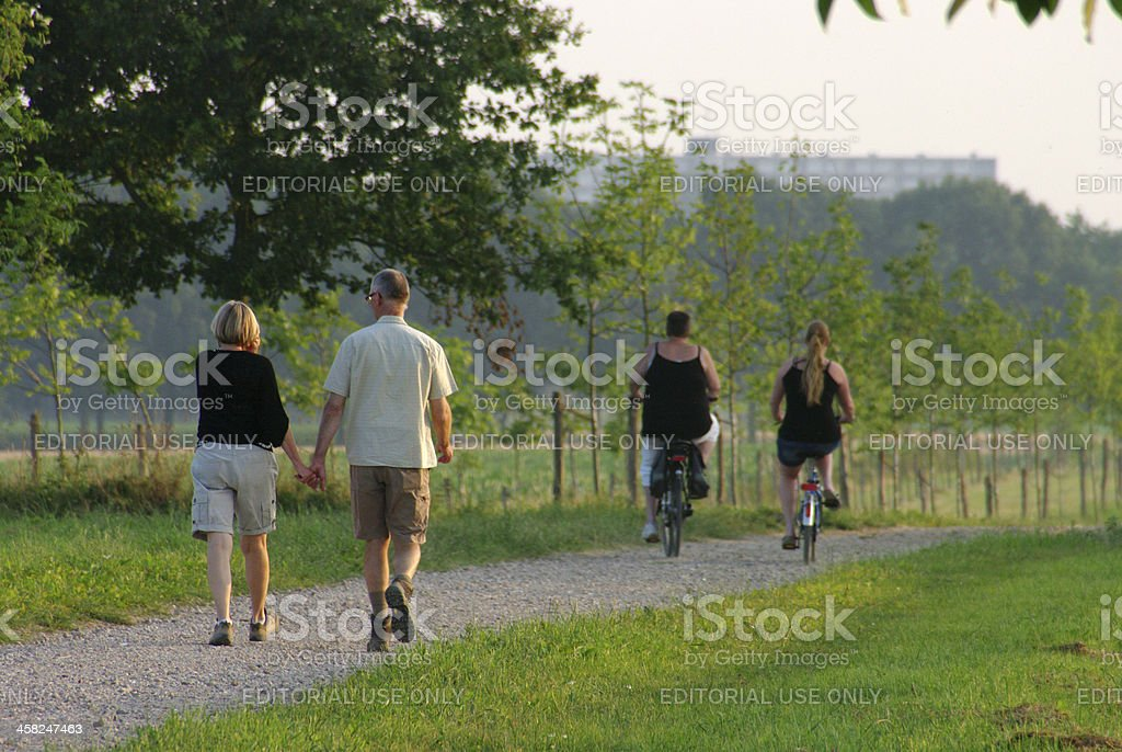 Walking and biking on a warm summer evening stock photo