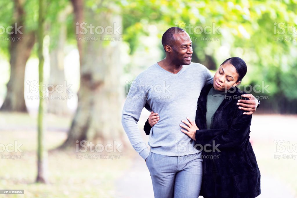 Walking and talking with an arm around the girlfriend stock photo