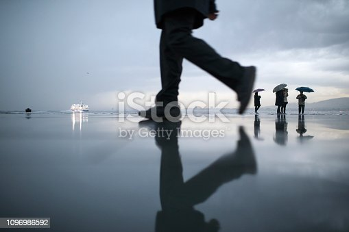 Silhouettes of walking people at rain reflections