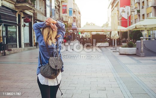 Beautiful blonde female walking away with backpack on her back