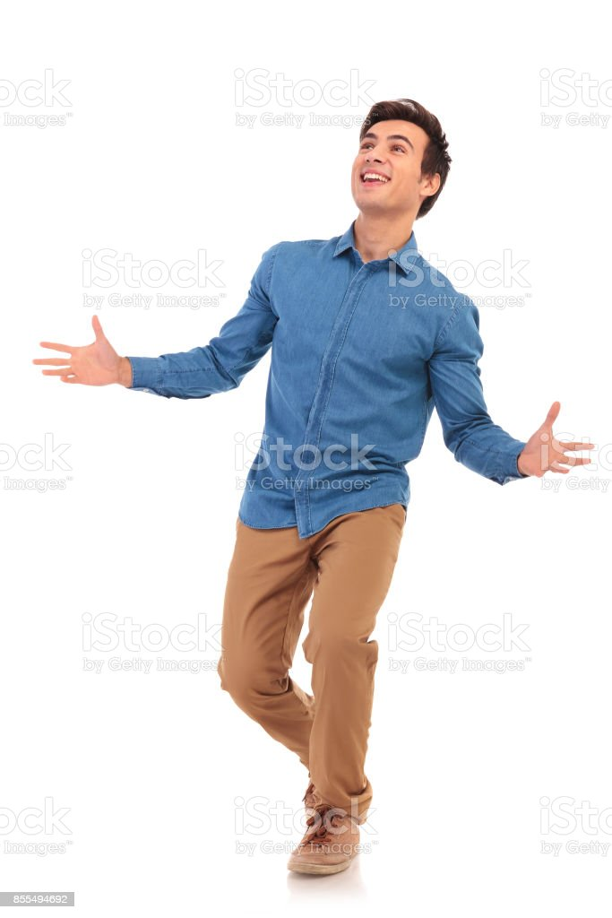 walking casual man welcoming and looking up amazed stock photo