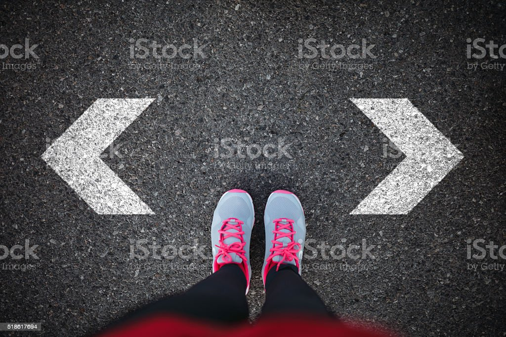Walking direction on asphalt Woman standing on asphalt looking down at arrow sign on asphalt and her choosing, Adult Stock Photo