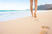 Woman walking down the beach in Hawaii, USA.