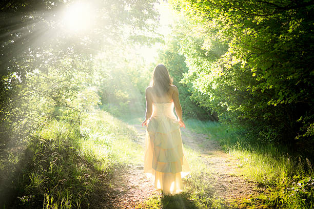 Walking fairy Beautiful young woman wearing elegant white dress walking on a forest path with rays of sunlight beaming through the leaves of the trees sun shining through dresses stock pictures, royalty-free photos & images